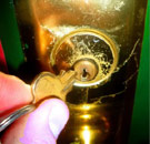 Gold apartment lock being opened by a key