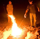 Guy squirting lighter fluid on a beach bonfire