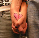 Guy and girl's hand interlocked with a heart drawn on