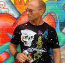 Guy wearing an Ed Hardy shirt in front of a graffiti wall