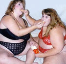 Two fat girls in bras feeding each other