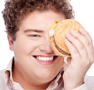 Fat and happy man holding a hamburger up to his eye