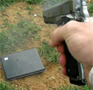 Gun shooting a laptop.