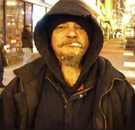 Homeless man staring straight ahead with cigarette in mouth
