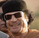 Momar Qaddafi smiling with sunglasses on