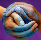 Hands together in a ball forming Planet Earth with blue paint