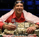 Poker player with a pile of cash winnings at poker table