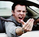 Man with road rage gesturing out his car window