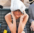 Scared woman with newspaper and hands on her head sitting on a bench