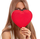 Girl holding a heart in front of her face