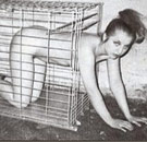 Naked woman crawling out of a cage