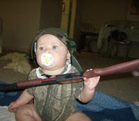 Baby holding a rifle