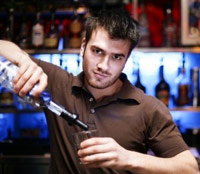 Male bartender pouring a shot