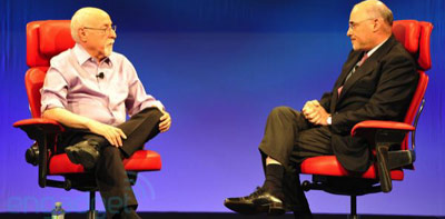 Two rich white CEO men sit on stage at a conference