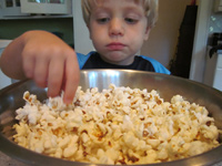 Child eating out of a popcorn bowl