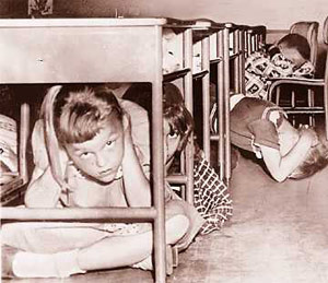 Children under desk for bomb drill during Cold War