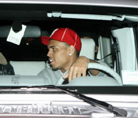 Chris Brown leaning over in the car yelling at Rihanna