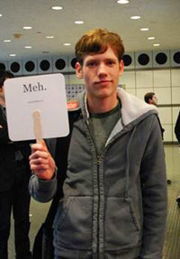 Christopher Poole holding up a 'Meh.' sign