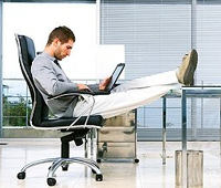 Man leaning back in a chair using his laptop at his desk