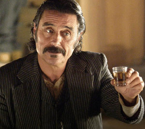 Guy from Deadwood TV show with a whiskey drink in hand