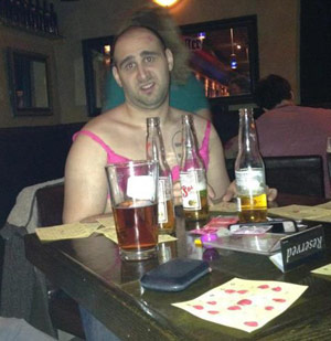 Guy drinking beers at a bar in a dress