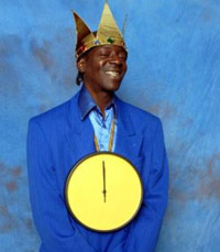Flava Flav in front of a blue backdrop wearing a clock