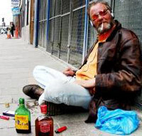 Homeless man sitting down with liquor bottles