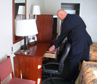 Man picking up a Bible out of a hotel room drawer