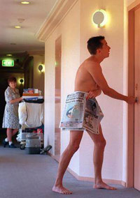 Guy in just newspaper outside his hotel room door