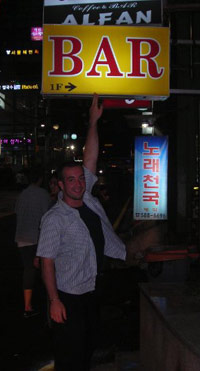 KC pointing to a BAR sign in Korea