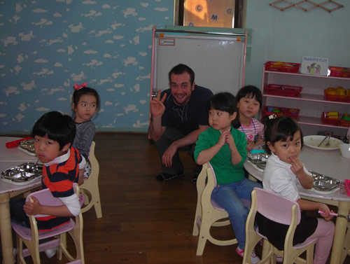 Korean children sitting in a classroom with American teacher
