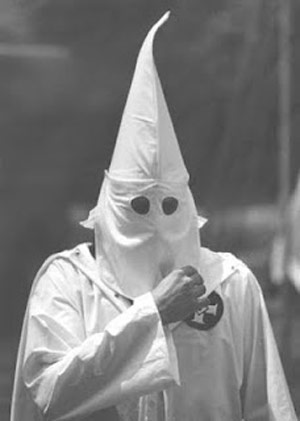 Ku Klux Klan member in a white robe and hood