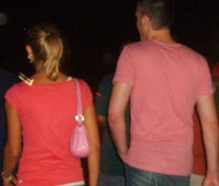 Guy in a pink shirt that matches his girlfriend's purse