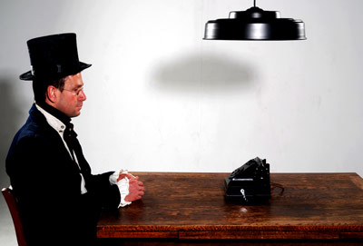 Man in a top hat waiting by the phone on a table