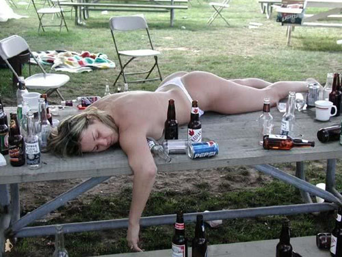 Woman passed out drunk on a picnic table amidst empty beer bottles