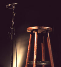 Microphone and stool on stage at open mic comedy night