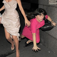 Girl falling down on the sidewalk in a pink dress