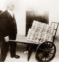 Man pushing a wheelbarrow of cash.