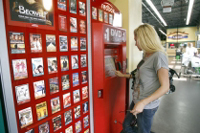 Woman renting a DVD from Redbox.