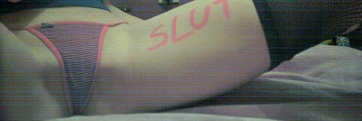 Slutty girl with 'slut' written in marker on her leg by her thong
