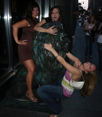 Three girls humping a statue of a lion
