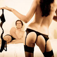 Woman doing a strip tease for her man in bed