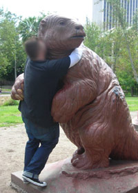 Guy hugging a bear statue in public