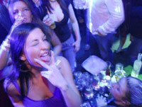 Girl sticking tongue out in VIP section of a club
