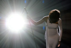 Whitney Houston in the spotlight on stage singing
