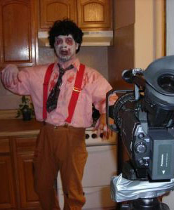 Casey dressed as a zombie in front of a video camera