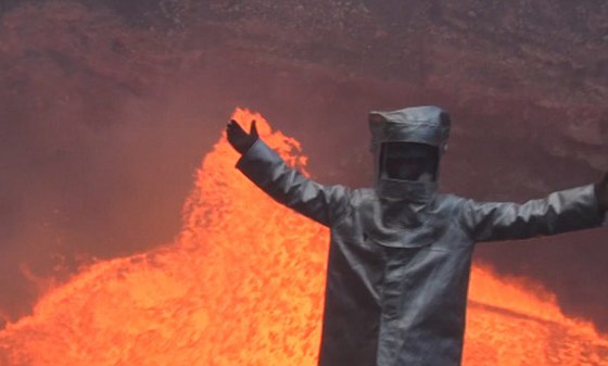Man in a suit next to an active volcano