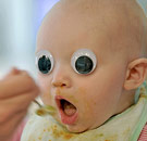 Baby with googly eyes eating food
