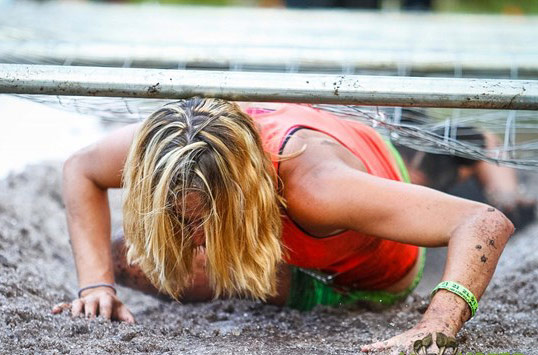 Woman goes under a barbed wire obstacle course