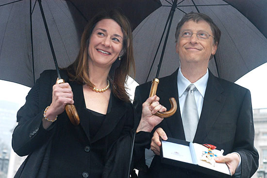 Bill and Melinda Gates standing under umbrellas